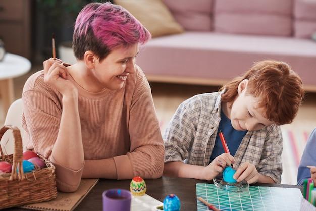 그녀의 아이가 집에 있는 테이블에서 부활절 달걀을 칠하는 것을 돕는 웃는 어머니