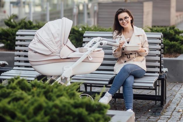 Madre sorridente che tiene in mano una scatola di plastica per il pranzo mentre è seduta su una panchina con passeggino e neonato
