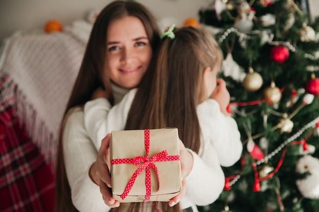 Улыбающаяся мать обнимает дочь с подарками в руках и рождественскими украшениями