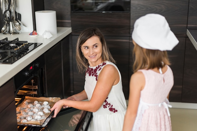 Smiling mother keeping cookies for baking in oven while looking at her daughter