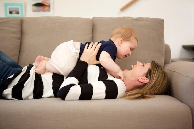 집에서 소파에 누워 그녀의 아들과 함께 놀고 웃는 어머니