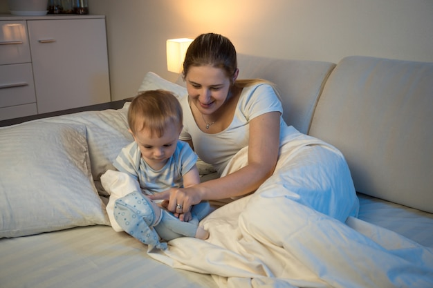 Smiling mother playing with her baby lying in bed at night and playing with toys