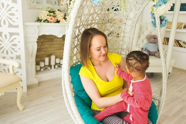 自宅で混血の赤ちゃんの息子と遊ぶ笑顔の母。
