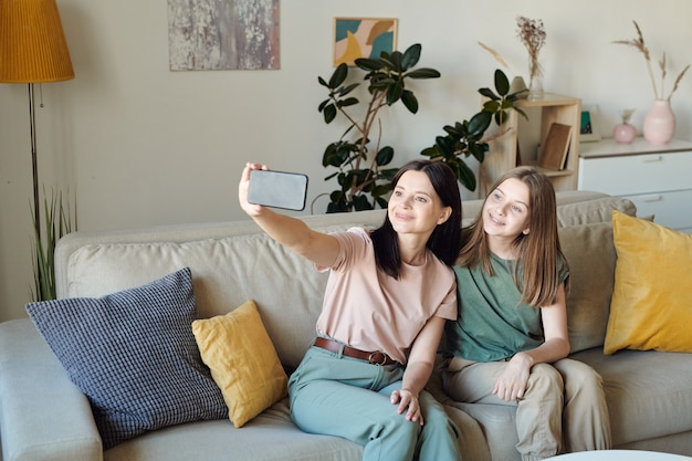 Улыбающаяся мать сидит на диване в гостиной и делает селфи с дочерью на смартфоне