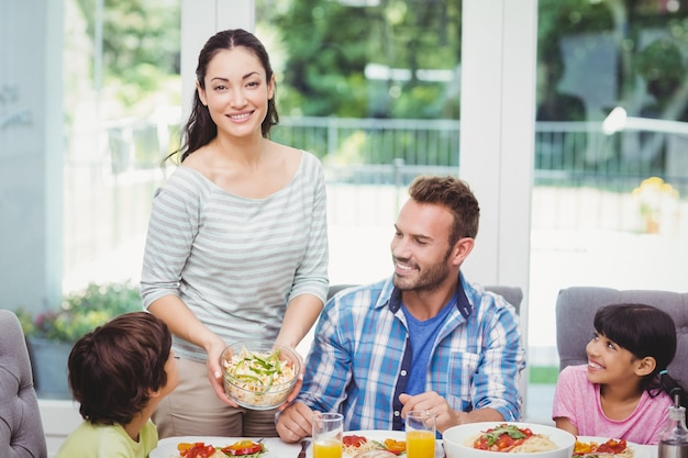 Smiling mother standing at dining table with family
