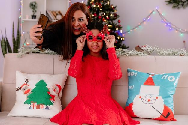Улыбающаяся мать фотографирует свою дочь в оленьих очках, сидящую на диване и наслаждающуюся рождеством дома