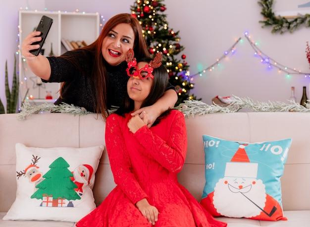 Sorridente madre prende selfie con sua figlia in maschera di renna seduto sul divano godendo il tempo di natale a casa