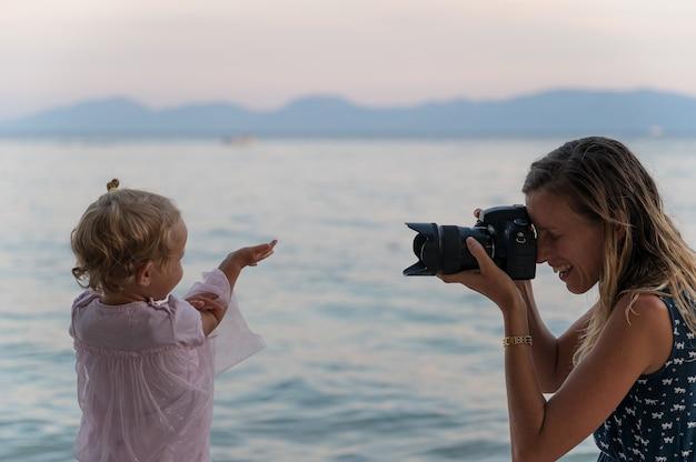 彼女の小さな幼児の娘の写真を撮る笑顔の母親