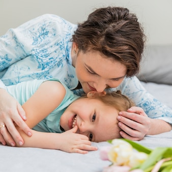 Smiling mother whispering in her small daughter's ear on bed