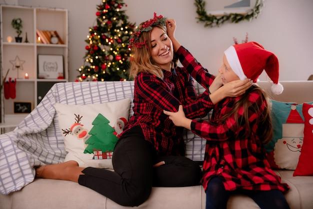 La madre sorridente con la corona di agrifoglio mette il cappello di babbo natale sulla figlia seduta sul divano e si gode il periodo natalizio a casa