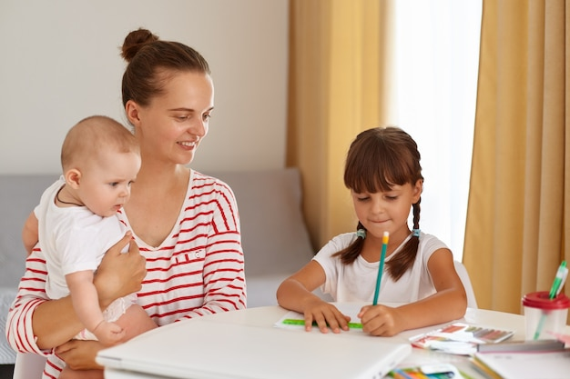 Smiling mother with new born baby in hands and elder daughter sitting at table and doing homework, dark haired girl in white t shirt writing in exercises book or drawing.