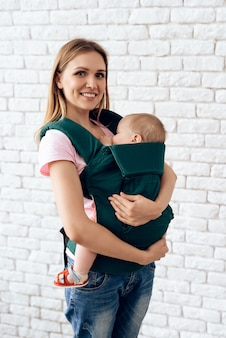 Smiling mother with newborn baby in baby sling.