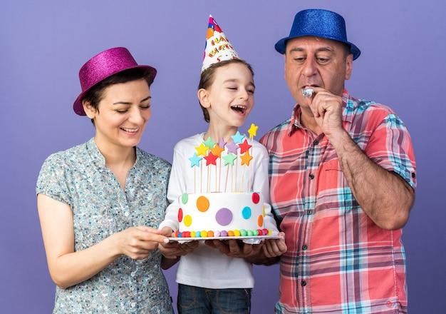 Madre sorridente con cappello da festa viola che tiene la torta di compleanno con il figlio che guarda il padre con cappello da festa blu che soffia fischio di festa isolato sulla parete viola con spazio di copia