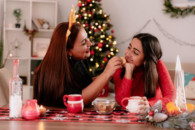 순록 머리띠와 함께 웃는 어머니는 집에서 크리스마스 시간을 즐기는 테이블에 앉아 기쁘게 딸을 피드