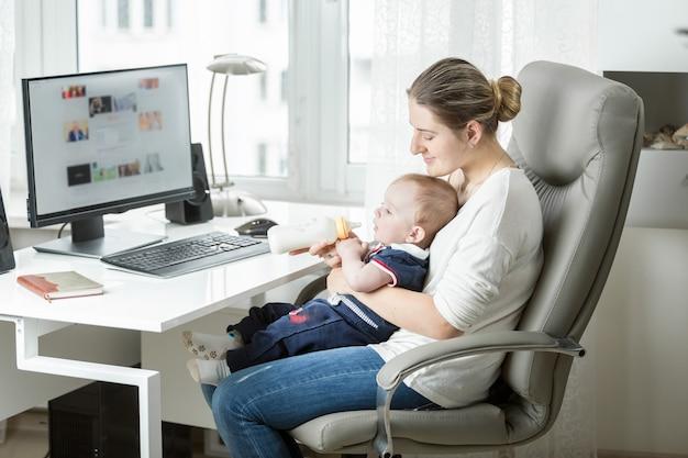 ホームオフィスで働いている笑顔の母親と哺乳瓶から赤ちゃんを養う