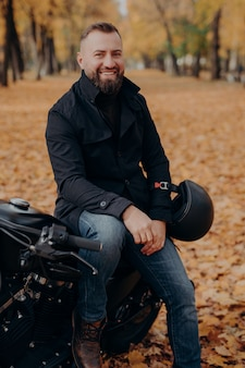 Smiling motorcyclist smiles happily, holds helmet, poses on motorbike, wears black jacket and jeans, has drive through park