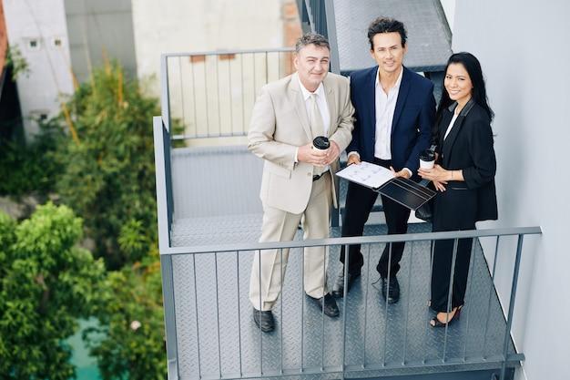 Улыбающаяся многонациональная бизнес-команда с финансовым отчетом стоит на пожарной лестнице и смотрит в камеру