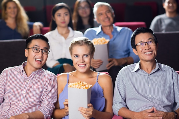 Smiling multiethnic audience watching movie Free Photo