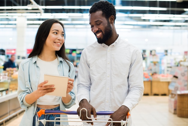 Smiling multiethnical couple buying goods in supermarket