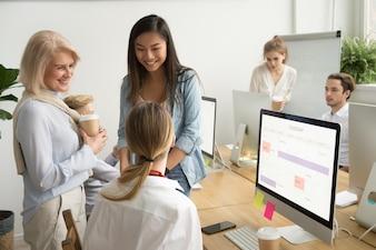 オフィスで話しているさまざまな年齢の多民族のビジネスウーマンの同僚の笑顔