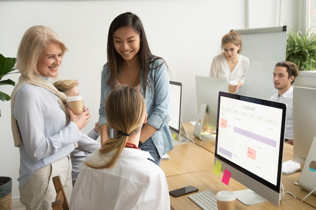 Улыбающиеся многорасовые предприниматели коллеги разного возраста разговаривают в офисе