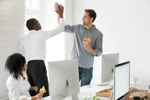 Smiling multiracial coworkers giving high-five eating pizza together at office
