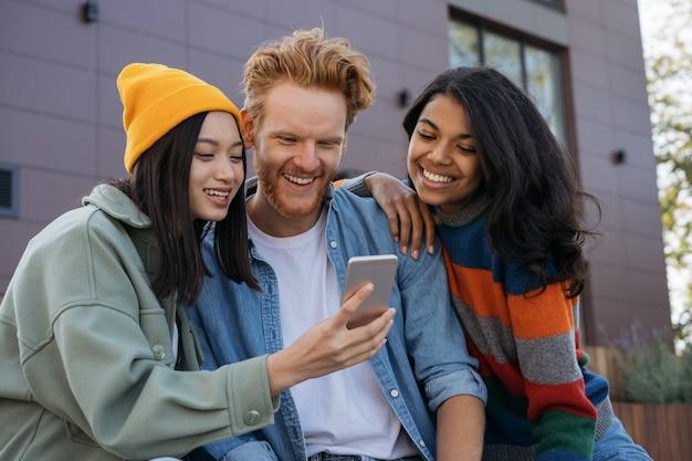 Улыбающиеся друзья из разных рас с помощью мобильного телефона смотрят видео онлайн