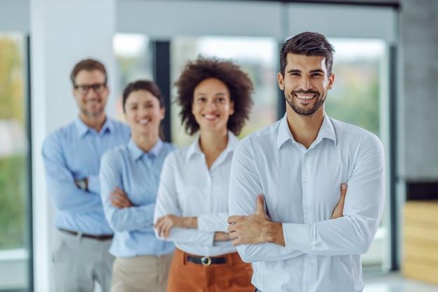 腕を組んで立って、オフィスに立っている間カメラを見ているビジネスマンの笑顔の多民族グループ。フォアグラウンドの男性に選択的に焦点を当てます。