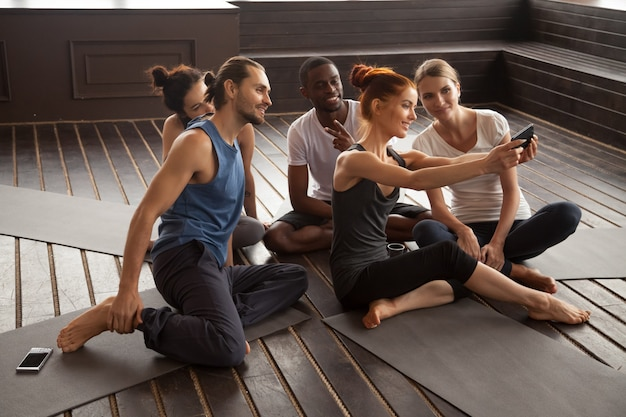 Smiling multiracial people making selfie on smartphone at yoga t