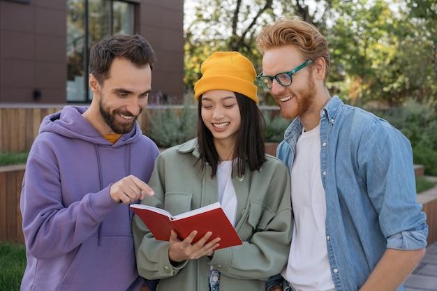 本の学習言語を読んで一緒に勉強している多民族の学生の笑顔