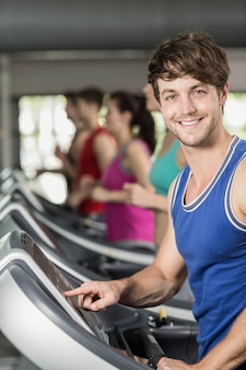 Smiling muscular man on treadmill at gym