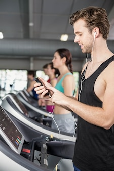Smiling muscular man on treadmill listening to music at gym