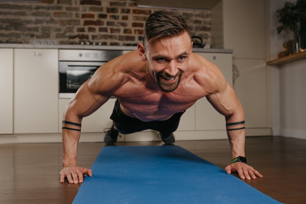 A smiling muscular man with a beard is doing pushups on a blue yoga mat in his apartment in the evening