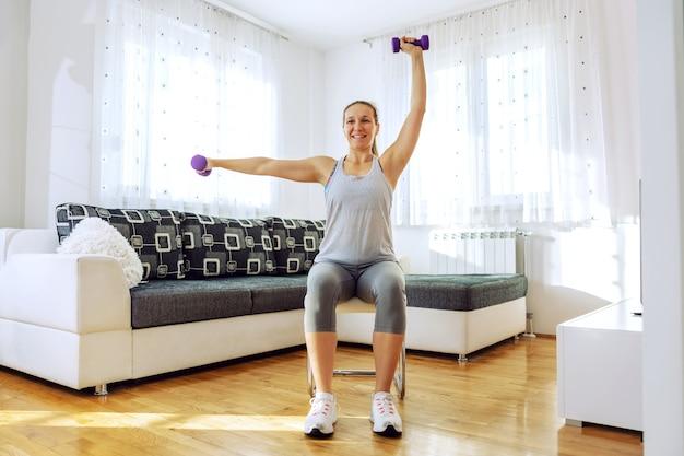 Улыбающаяся мускулистая спортсменка сидит на стуле у себя дома и делает фитнес-упражнения на руки с гантелями.