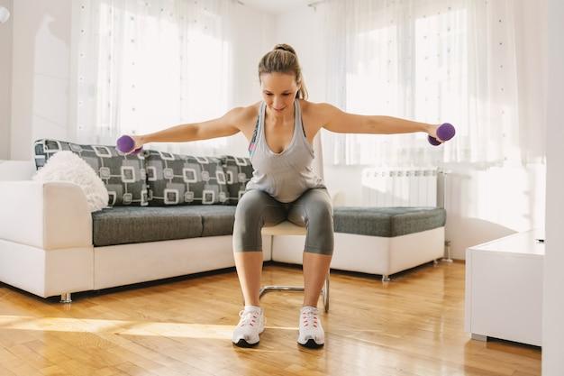 Улыбающаяся мускулистая женщина в форме сидит на стуле у себя дома и делает фитнес-упражнения для рук с гантелями.