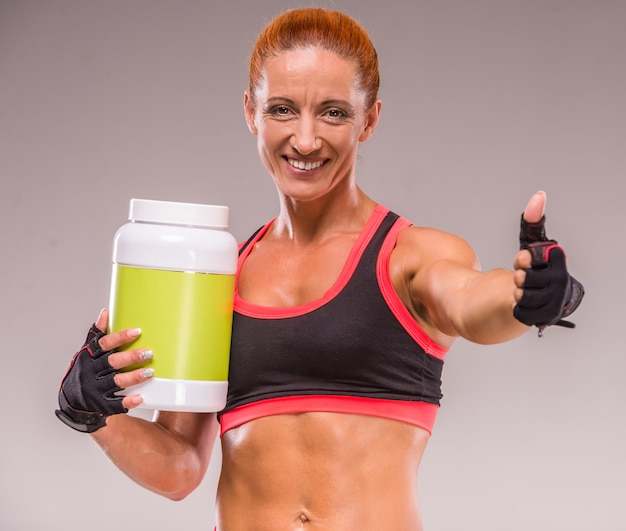 Smiling muscular woman with jar of protein.