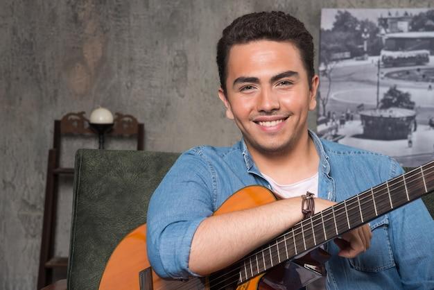 Musicista sorridente che tiene una bella chitarra e che si siede sul sofà