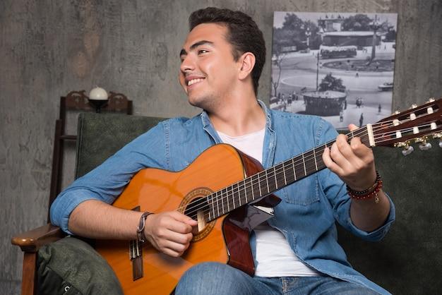 ギターを弾き、ソファに座って笑顔のミュージシャン。高品質の写真