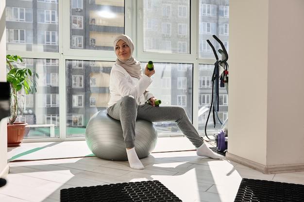 집에서 아령으로 운동하는 hijab 이슬람 소녀 미소, 맞는 공에 앉아있는 동안 멀리보고