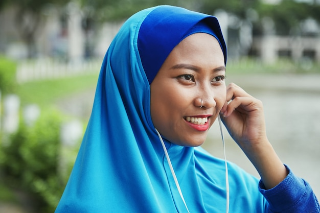 Smiling muslim woman plugging earphones on street