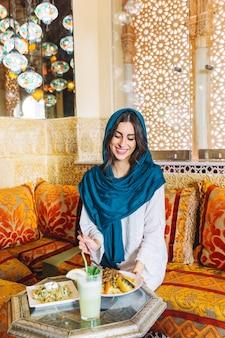 Donna musulmana sorridente nel ristorante