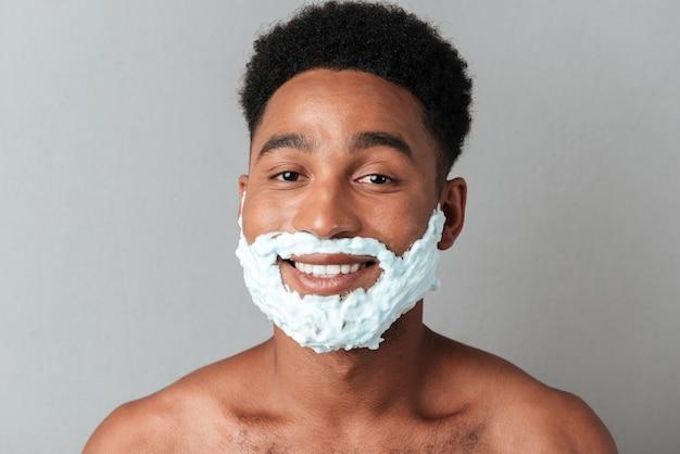 Uomo africano nudo sorridente con il viso in schiuma da barba