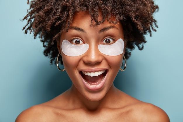 웃는 알몸의 여성은 건강한 피부, 눈 밑에 화장 패치, 미용 또는 눈 치료, 주름 제거, 넓은 미소, 완벽한 하얀 치아, 벌거 벗은 어깨가 있습니다. 자연스러운 메이크업