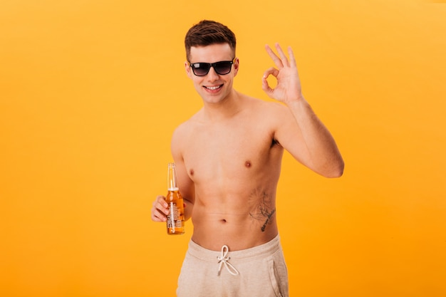 Smiling naked man in shorts and sunglasses holding bottle of beer and showing ok sign over yellow