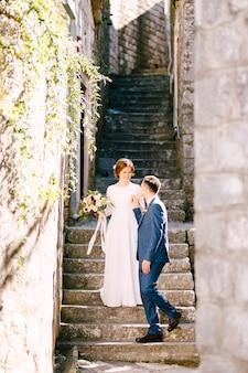 웃는 신혼 부부는 신랑이 아름다운 꽃다발로 사랑스러운 신부에게 손을 준 계단을 내려갑니다.