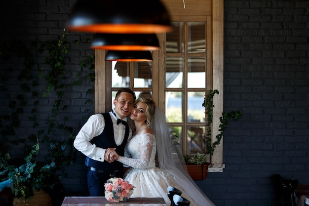 Smiling newlyweds hugging near the window indoor. portrait of newlyweds in stylish hotel room. wedding couple in a room with a stylish interior with lamps. wedding day
