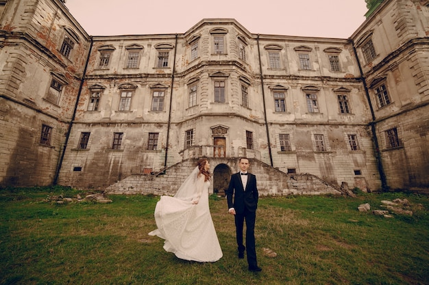 Smiling newlyweds with ancient castle background