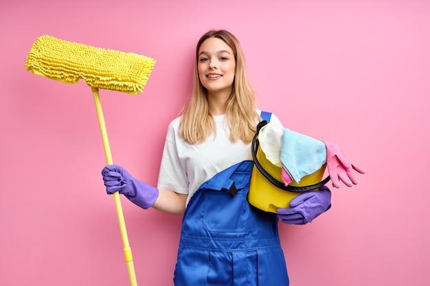 파란색 작업복과 고무 장갑에 웃는 좋은 백인 여자는 청소 용품을 들고 카메라를 봐.