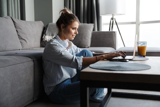Улыбается милая женщина с наушниками, используя ноутбук, сидя на полу в гостиной