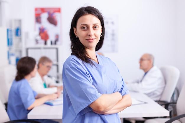 バックグラウンドで医療スタッフとカメラを見ている病院の会議室で青い制服を着て笑顔の看護師。クリニックの会議室、ローブ、スペシャリストのフレンドリーな開業医。